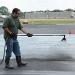 A professional applicator applies coal-tar-based sealcoat to a test plot used to measure emission of polycyclic aromatic carbons (PAHs) into the air