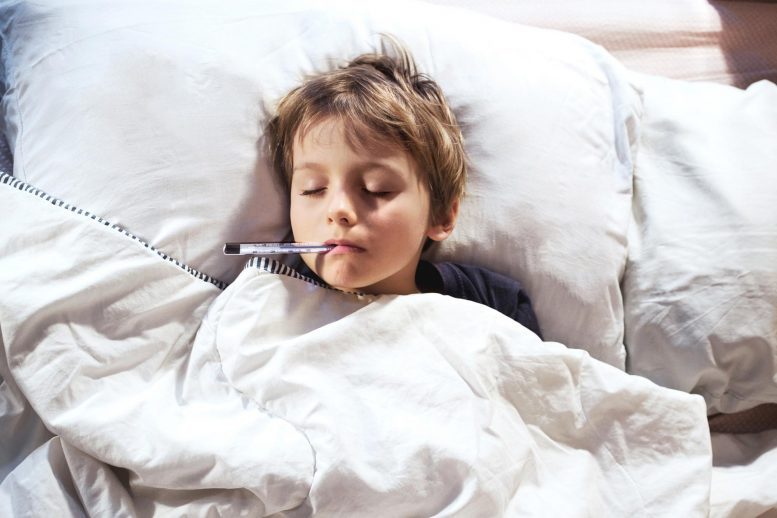 Child Sick in Bed With Thermometer