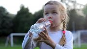 Girl Drinking From Plastic Water Bottle