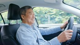 Happy Elderly Man Driving Car