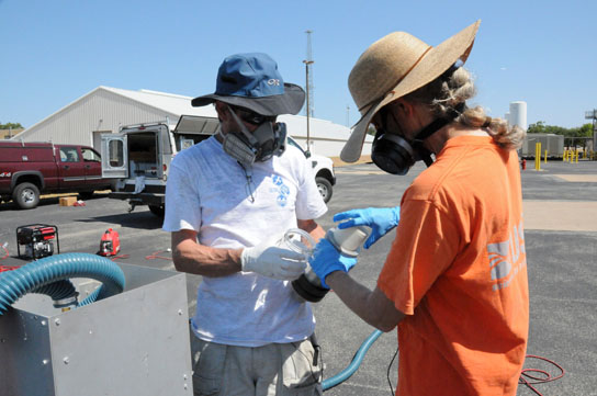 USGS scientists prepare a sampler used to measure emission of polycyclic aromatic carbons (PAHs) into the air