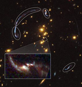 brightest galaxy, whose image has been distorted by the gravity of a distant galaxy cluster