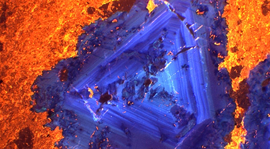 True-colour cathodoluminescence image taken with the Cameca SX100. Fluorite (blue-violet) is shown associated with calcite (yellow-orange) in a carbonatite from India. Credit: Natural History Museum UK