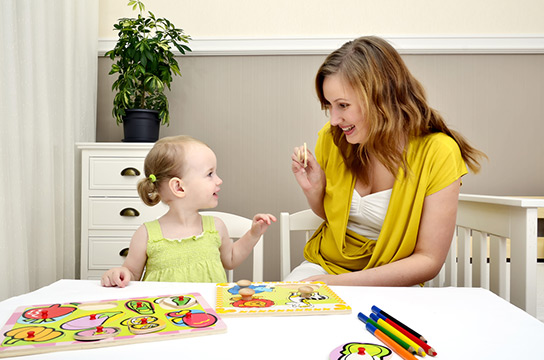 Mom Helping Child With Puzzle