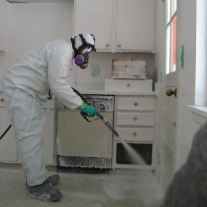 remediator sprays Crystal Clean on surfaces of a house contaminated with methamphetamine