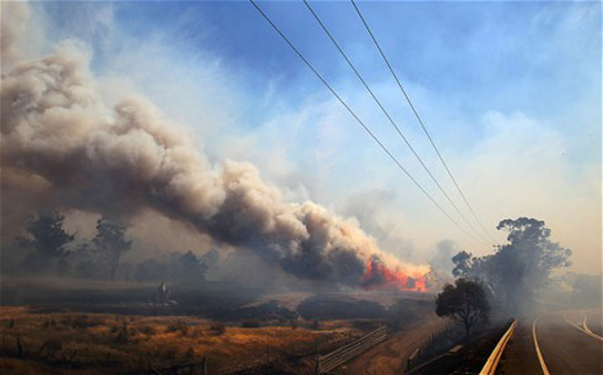 Thick smoke rises from a burning property in Dunalley, Tasmania, Australia. Credit: Richard Jupe/Newspix / Rex Features